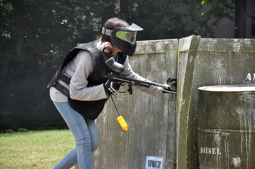 Girl hiding while playing paintball